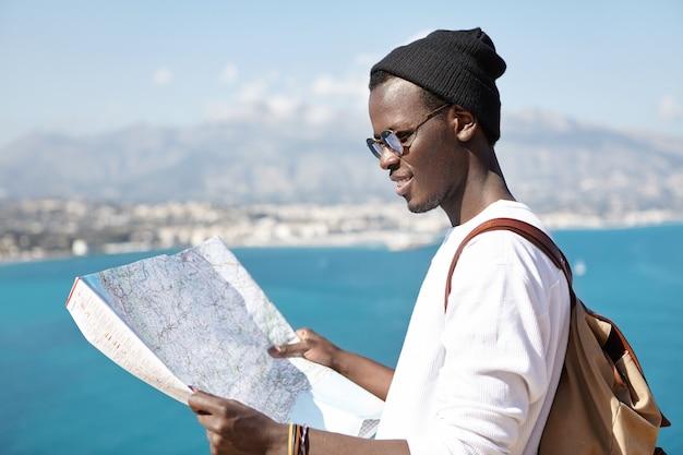 Vista lateral de um jovem caroneiro sorridente, estudando um mapa de papel nas mãos