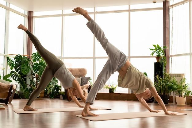 Vista lateral de um jovem casal ativo em roupas esportivas, inclinando-se para a frente enquanto fica de pé em esteiras com uma perna esticada durante o treino em casa