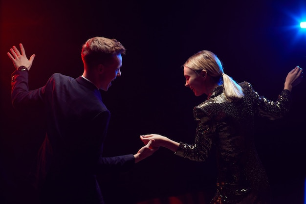 Vista lateral de um jovem casal feliz dançando juntos enquanto aproveitava a festa na noite do baile contra um fundo preto