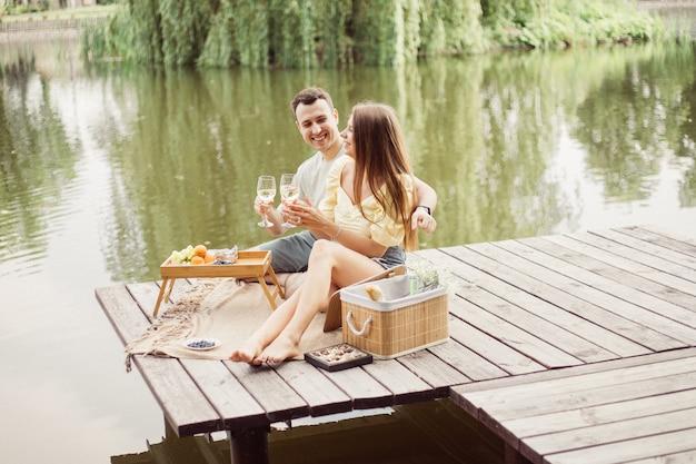 Vista lateral de um jovem casal feliz em um piquenique romântico perto do rio ou lago, mulher e homem bebendo vinho ao ar livre juntos, pessoas se divertindo nas férias de verão, foto do estilo de vida