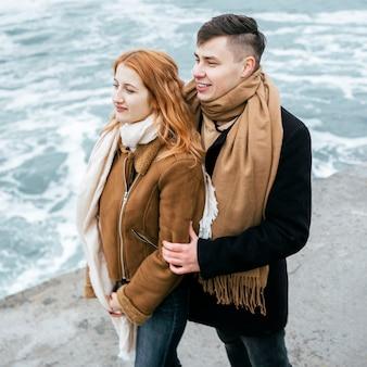 Vista lateral de um jovem casal no inverno lá fora