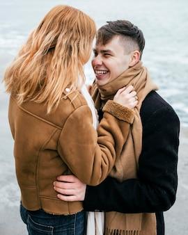 Vista lateral de um jovem casal no inverno