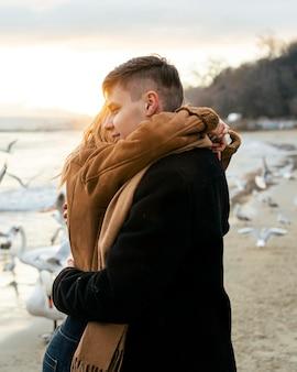 Vista lateral de um jovem casal se abraçando na praia no inverno