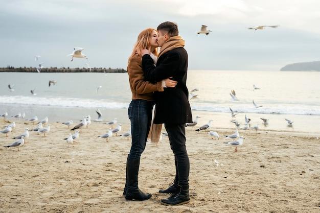 Vista lateral de um jovem casal se beijando no inverno na praia