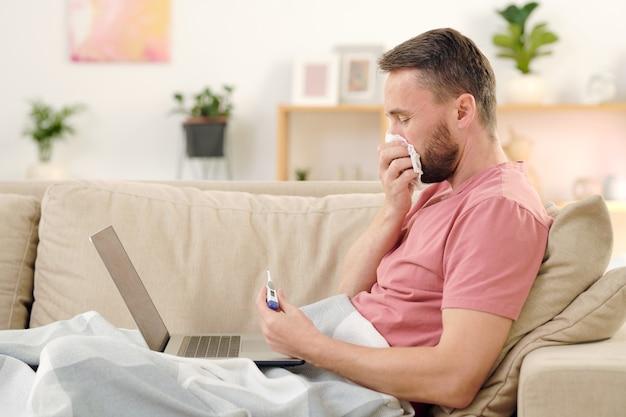 Vista lateral de um jovem doente olhando para o termômetro e assoando o nariz enquanto está sentado no sofá, debaixo do cobertor, consultando um médico on-line
