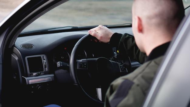 Vista lateral de um jovem elegante e confiante dirigindo seu carro