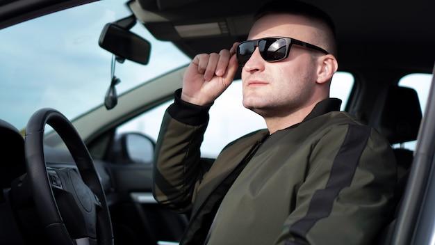 Vista lateral de um jovem elegante e confiante em óculos de sol, dirigindo seu carro