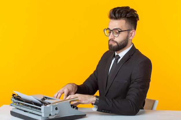 Vista lateral de um jovem empresário encantador em trajes formais e óculos, digitando em um texto de máquina de escrever. conceito de negócios e ideias. lugar para promoção