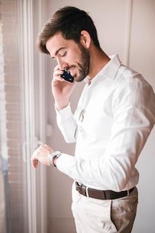 Vista lateral de um jovem empresário feliz falando no celular