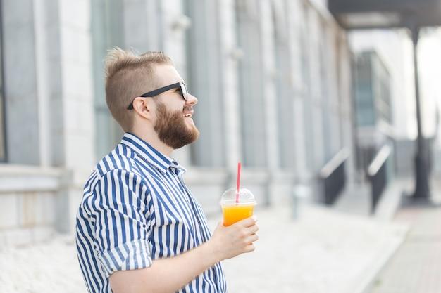 Vista lateral de um jovem empresário muito alegre, com um bigode elegante e uma barba com suco nas mãos, andando pela cidade após um dia de trabalho. conceito de positivo e descanso.
