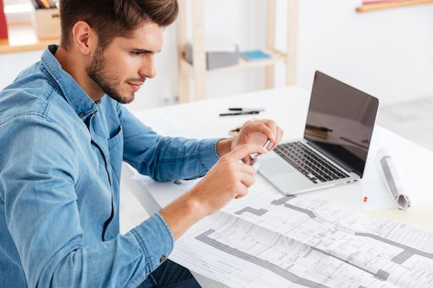 Vista lateral de um jovem empresário tirando foto de documentos com o smartphone enquanto está sentado na mesa do escritório