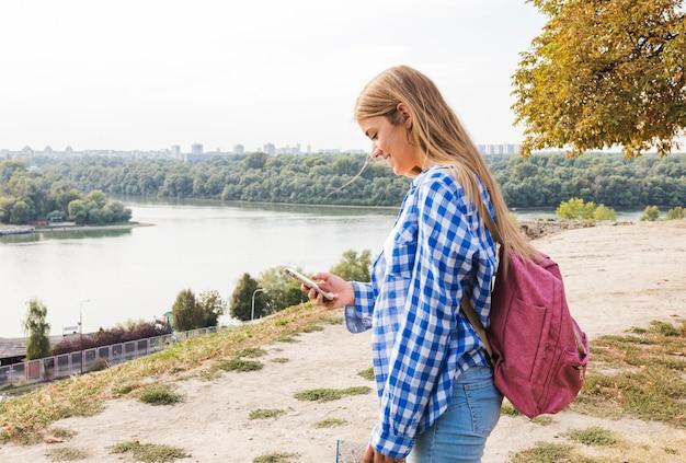 Vista lateral, de, um, jovem, femininas, hiker, usando, cellphone