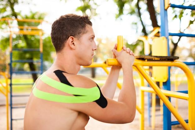 Vista lateral de um jovem fisiculturista profissional caucasiano com fitas elásticas pretas e verdes nos ombros, posando em campo esportivo