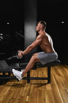 Vista lateral de um jovem forte com corpo atlético, fazendo exercícios em equipamentos de fitness em uma motivação de fitness ginásio escuro