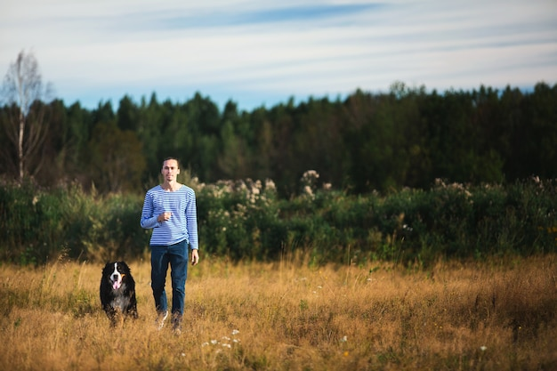 Vista lateral de um jovem homem caucasiano treinando bernese mountain dog no campo de verão