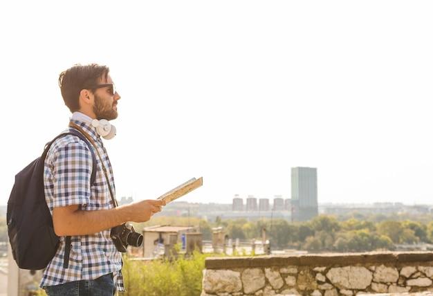 Vista lateral, de, um, jovem, macho, hiker, com, mapa