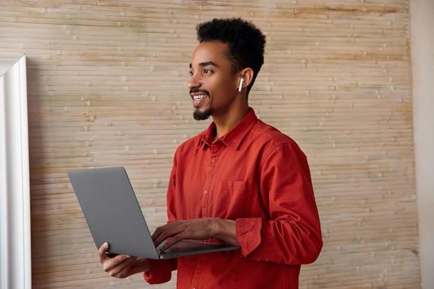 Vista lateral de um jovem moreno de cabelos curtos, pele escura, segurando o laptop nas mãos levantadas e olhando para o lado com um sorriso encantador, de pé no interior bege
