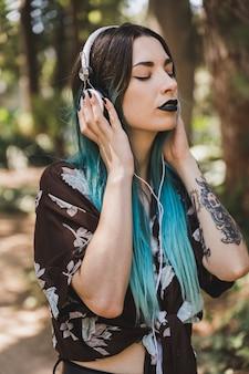 Vista lateral, de, um, jovem, mulher moderna, escutar música, ligado, branca, auscultadores