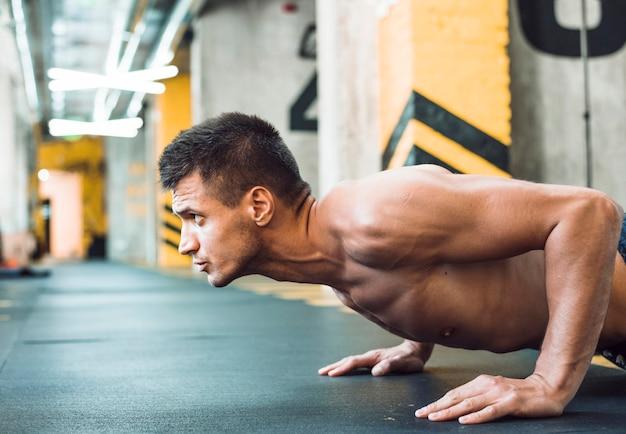 Vista lateral de um jovem musculoso fazendo flexões