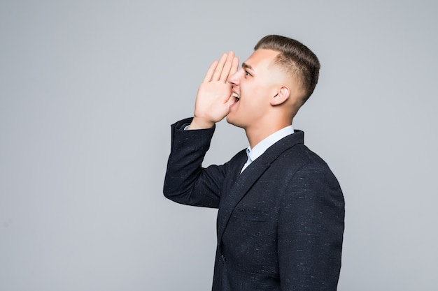 Vista lateral de um jovem segurando seu braço perto da boca e gritando algo