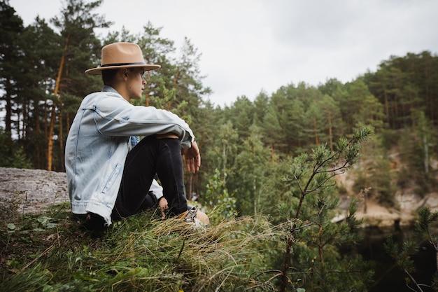 Vista lateral de um jovem viajante sentado na margem pedregosa admirando a paisagem do lago cercado