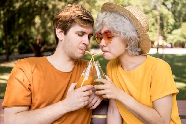Vista lateral de um lindo casal bebendo suco ao ar livre com canudos
