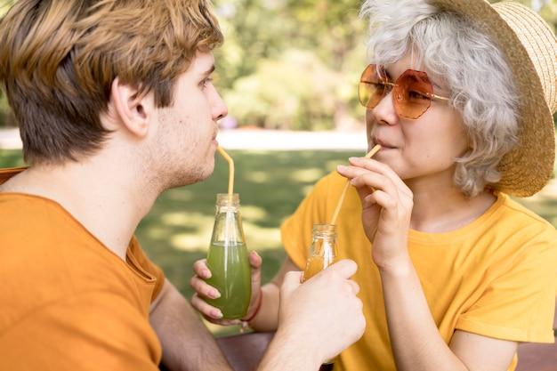 Vista lateral de um lindo casal bebendo suco no parque com canudos