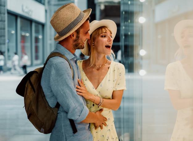 Vista lateral de um lindo casal dando uma olhada nas vitrines caminhando pela cidade