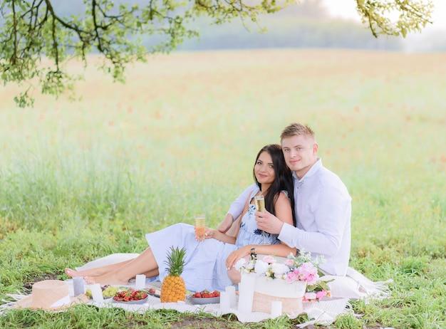 Vista lateral de um lindo casal em um piquenique sentado e se abraçando enquanto toma uma bebida