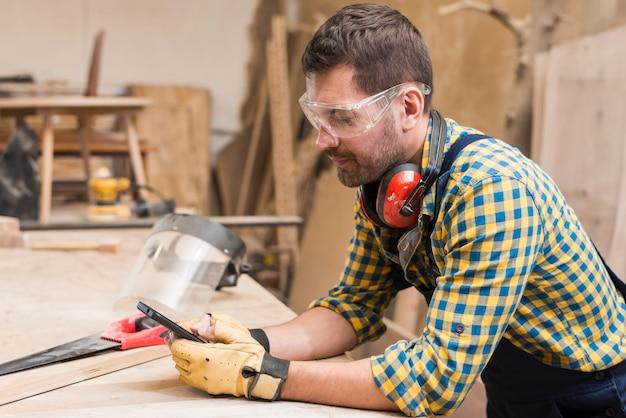 Vista lateral, de, um, macho, carpinteiro, usando, telefone móvel, em, a, oficina