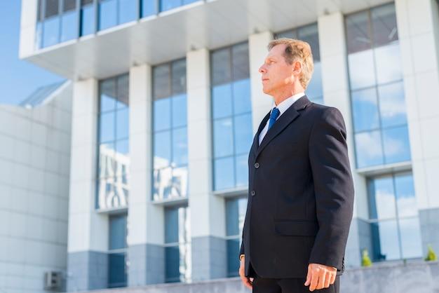 Vista lateral, de, um, maduras, homem negócios fica, frente, predios, em, ao ar livre