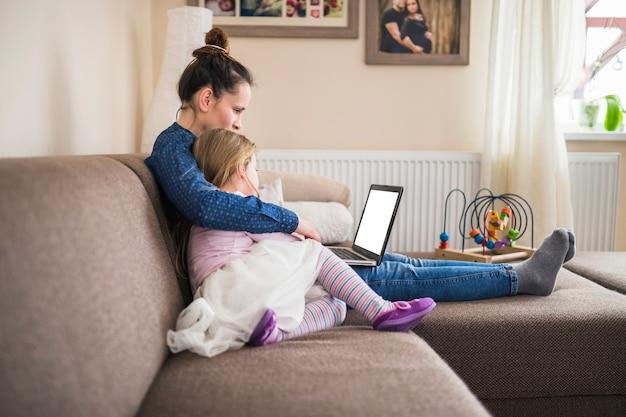 Vista lateral, de, um, mãe senta-se, com, dela, filha, usando computador portátil