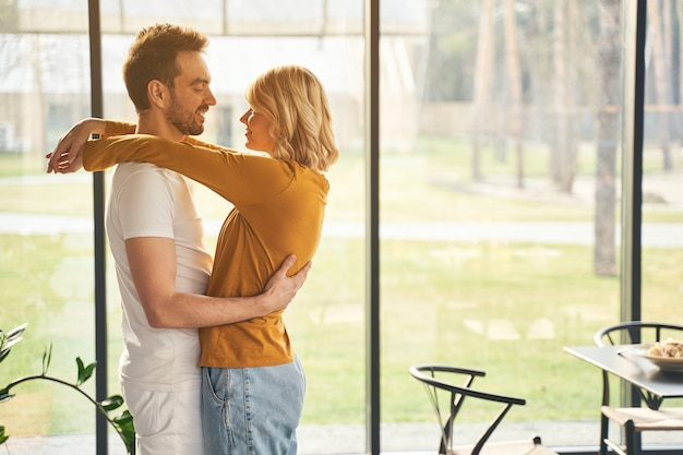 Vista lateral de um marido caucasiano atraente e feliz olhando com ternura para sua esposa sorridente e satisfeita