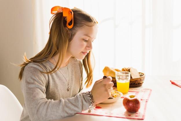 Vista lateral, de, um, menina, comer, fresco, saudável, pequeno almoço