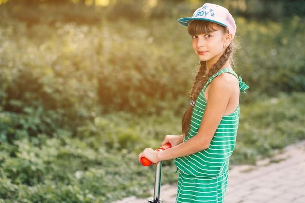 Vista lateral, de, um, menina, desgastar, boné, ficar, ligado, pontapé scooter