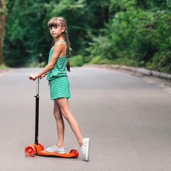 Vista lateral, de, um, menina, estar, a, scooter, ligado, estrada