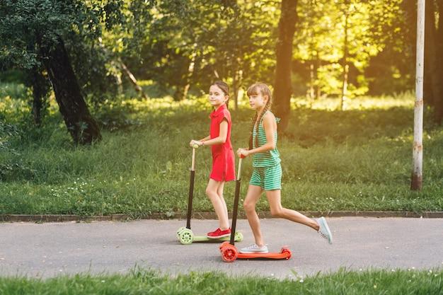 Vista lateral, de, um, meninas, montando, pontapé scooter, parque