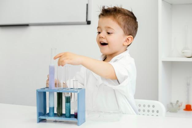 Vista lateral de um menino cientista no laboratório fazendo experimentos com tubos de ensaio