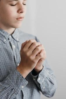 Vista lateral de um menino rezando de perto