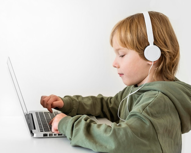 Vista lateral de um menino usando um laptop com fones de ouvido