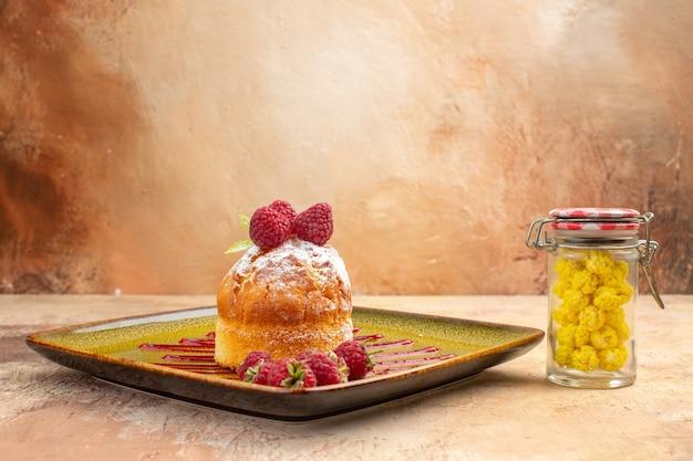 Vista lateral de um mini-bolo com frutas em um prato verde e doces em fundo de cor mista