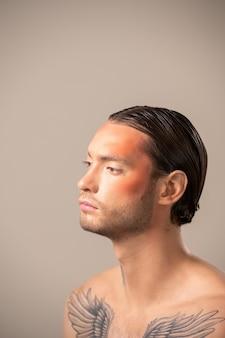 Vista lateral de um modelo jovem sério com maquiagem de palco, penteado preciso e tatuagem no peito e no pescoço