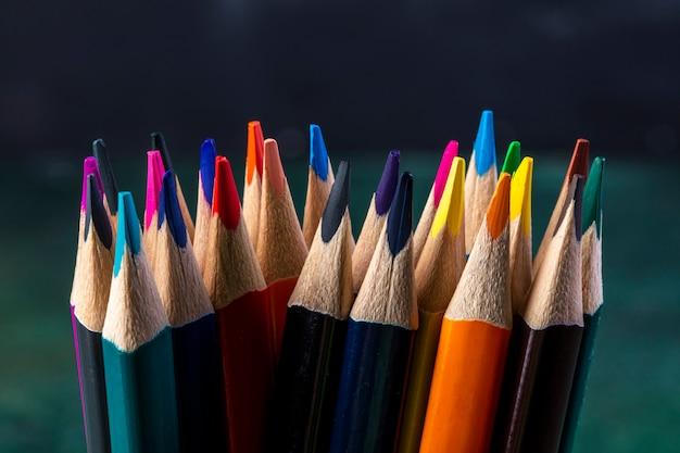 Vista lateral de um monte de lápis de cor no escuro