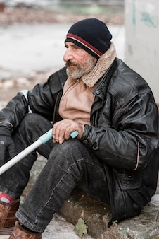 Vista lateral de um morador de rua segurando uma bengala