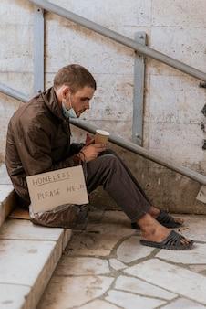 Vista lateral de um morador de rua segurando uma xícara e um cartaz de ajuda