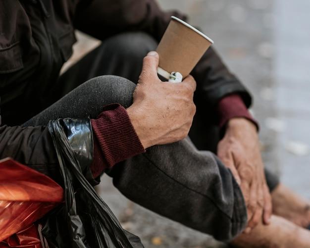 Vista lateral de um morador de rua segurando uma xícara