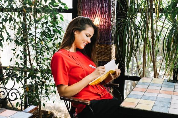 Vista lateral, de, um, mulher jovem, escrita, cronograma, em, diário