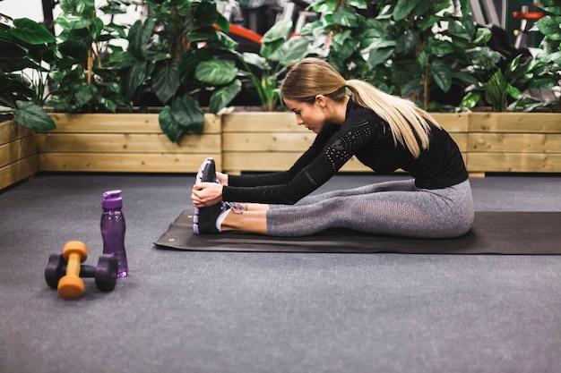 Vista lateral, de, um, mulher jovem, esticar, dela, perna, em, ginásio