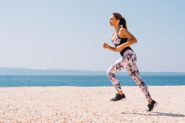 Vista lateral, de, um, mulher jovem, executando, ligado, praia