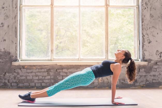 Vista lateral, de, um, mulher jovem, fazendo, ioga, ligado, esteira exercício